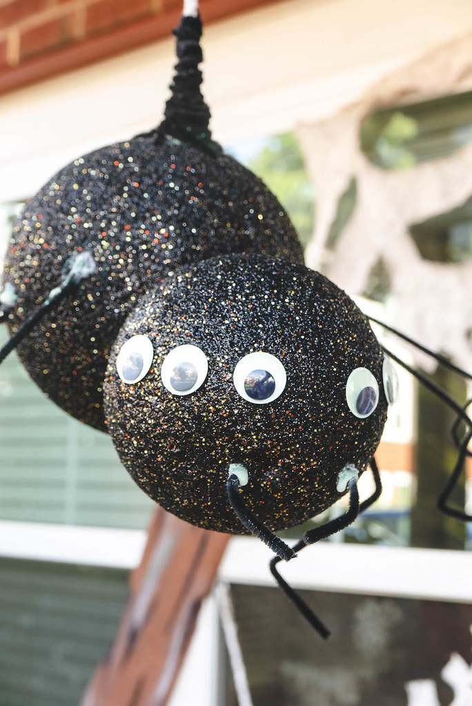 A huge Halloween spider attached by a rope and hang from the porch. The spider has googly eyes.