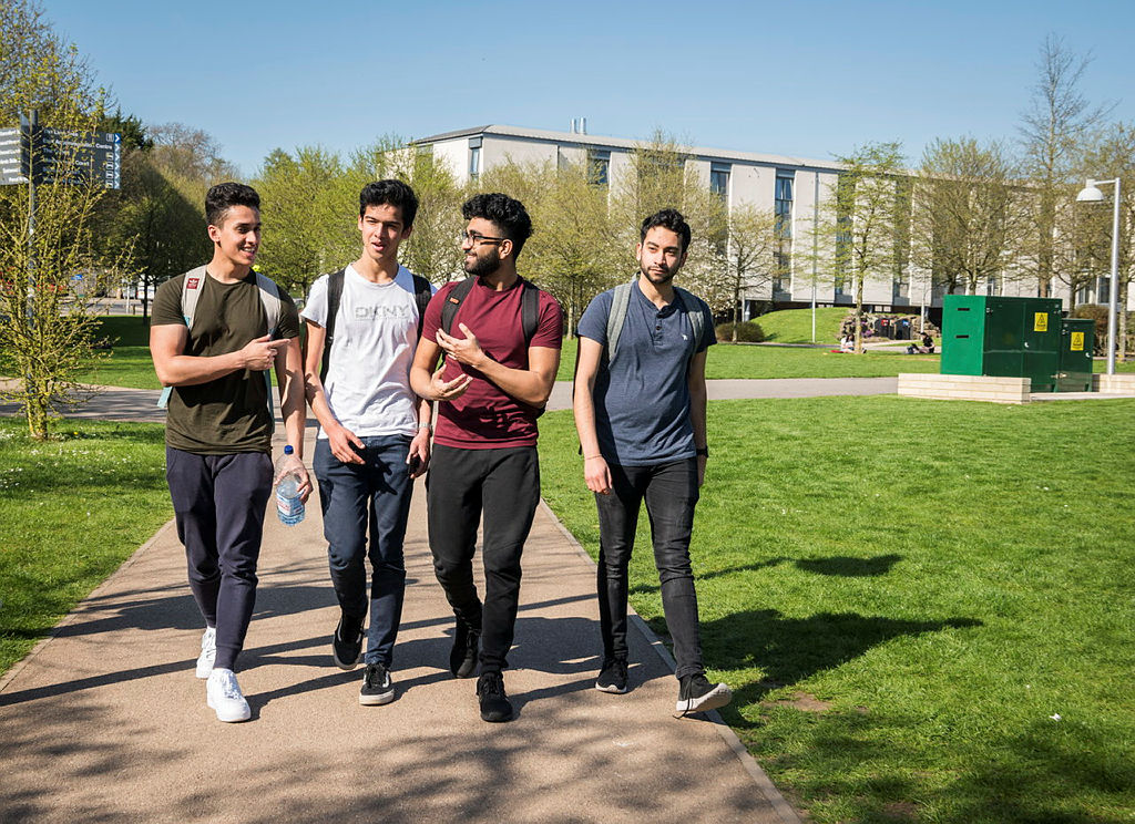 Four students walking together on campus