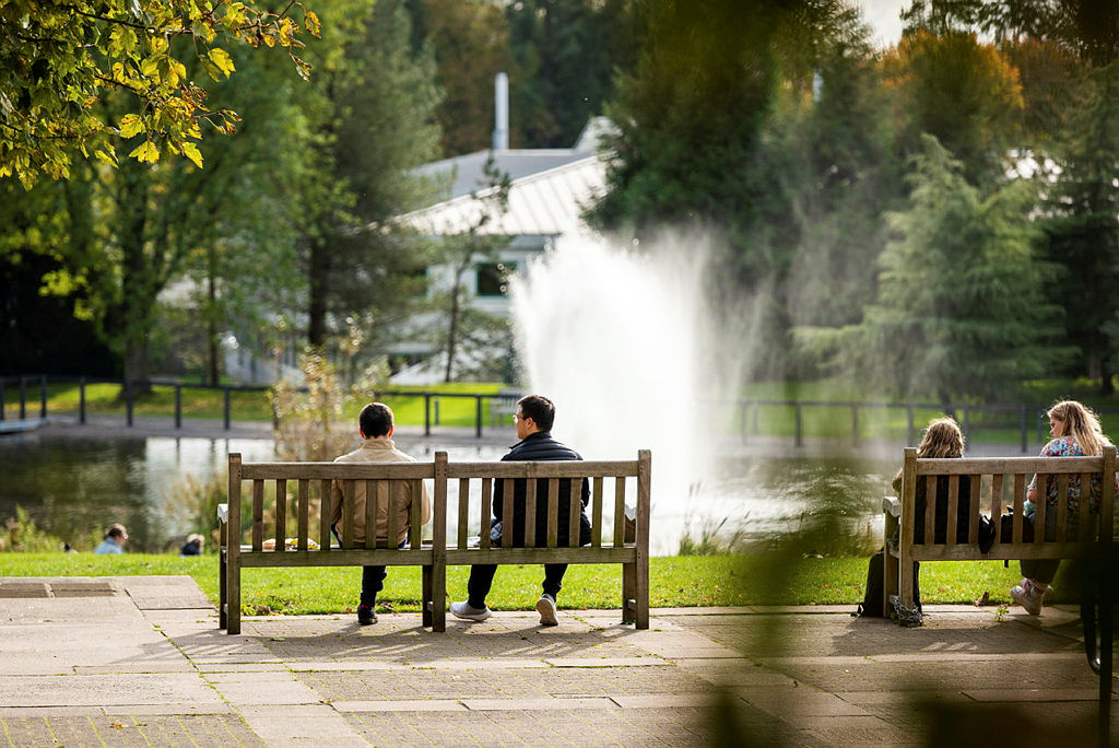 Students sat on benches by lake on campus