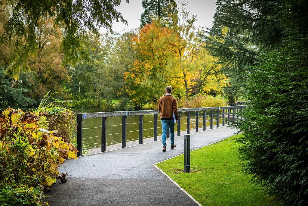 Student walking past lake on campus