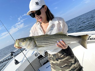 Photo of woman on a boat holding a striped bass