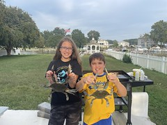 Photo of boy and girl holding blue crabs