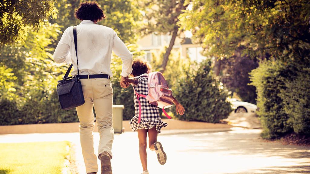 父亲和女儿步行去上班和上学.