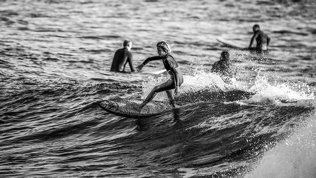 Young surfer catching a wave in black and white