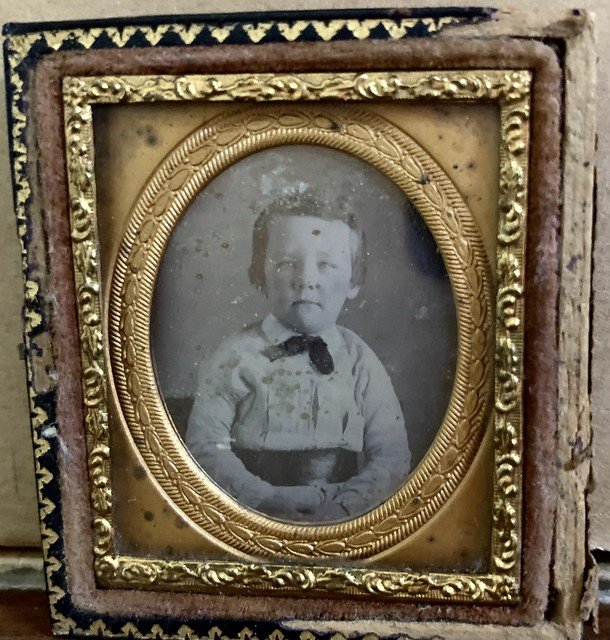 A small cased photograph of a little boy / or girl