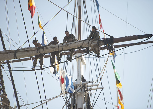 Sailors assigned to USS Constitution bend on Constitution's forward top sail.