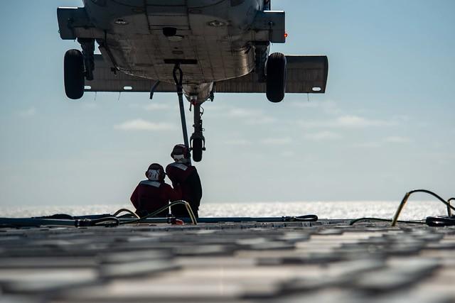 Sailors attach cargo to an MH-60S Sea Hawk helicopter aboard USS Ronald Reagan (CVN 76).