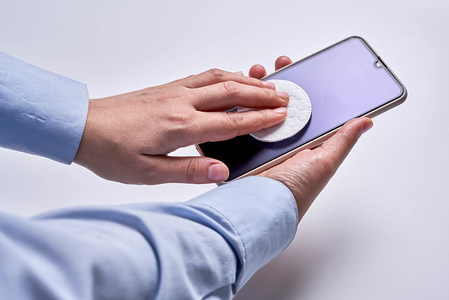 Woman cleaning display of smart phone with antibacterial white tissue or disposable wipe