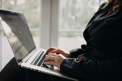 Senior woman in striped jacket sitting near window and typing on her laptop at home.