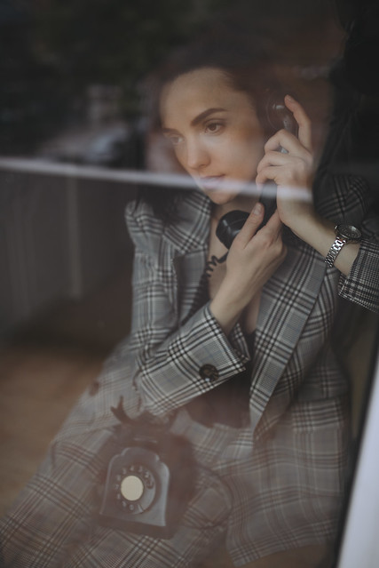 Woman looking through the window while talking on a rotary telephone.