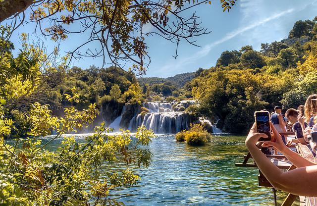 Touristen auf der Brücke am Wasserfall