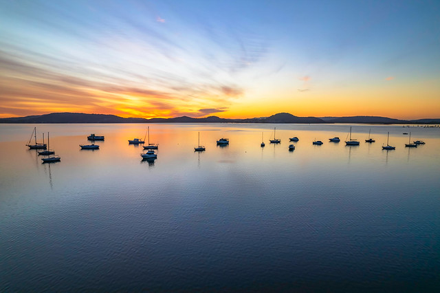 Aerial sunrise waterscape with boats and high cloud
