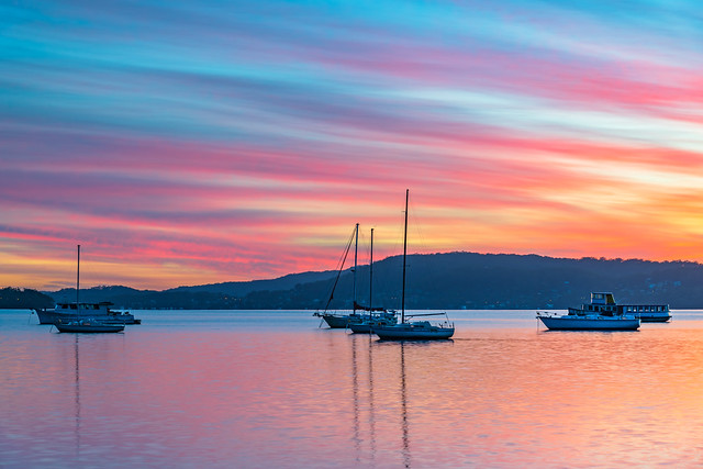 Sunrise waterscape with boats, reflections and high cloud
