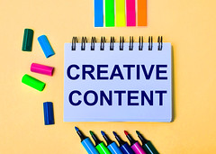 On a beige background, a notebook with the words CREATIVE CONTENT, bright felt-tip pens and stickers