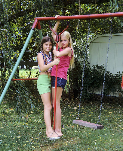 """We had the coolest swings in our back yard. My sister and a friend stand on the """"twirler"""", a swing which also spun around.  There was also a hanging bar and a two-person swing, which with enough inertia, flew quite high. Milford CT. Aug 1974"""