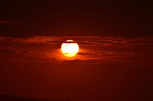 Orange setting sun shining through clouds