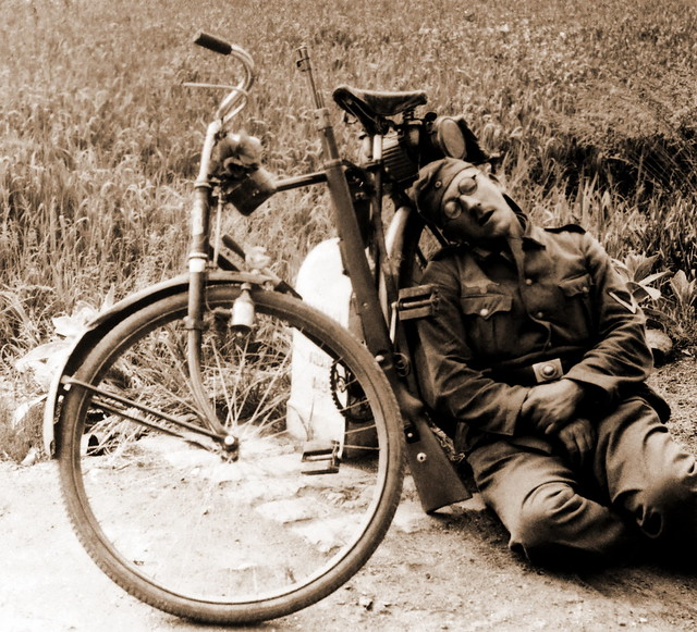 An exhausted German soldier takes a nap with his Mauser K98 resting next to him during WW2