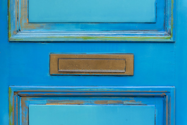 Blue green door with a letterbox