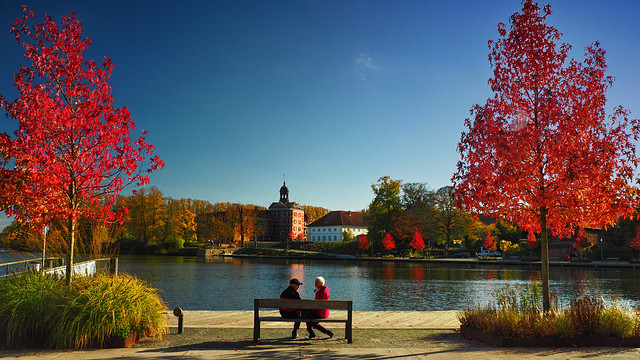 The city bay on Lake Eutin is presented in the most glorious red. Numerous red maple trees shine in competition.  In the background you can see the Eutin Castle