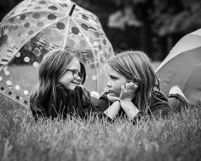 The girls in the park with umbrellas.