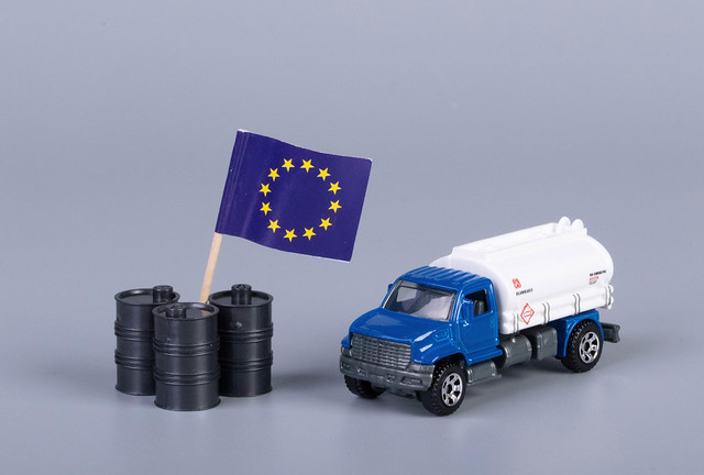 Oil truck and oil barrels with flag of European Union on grey background