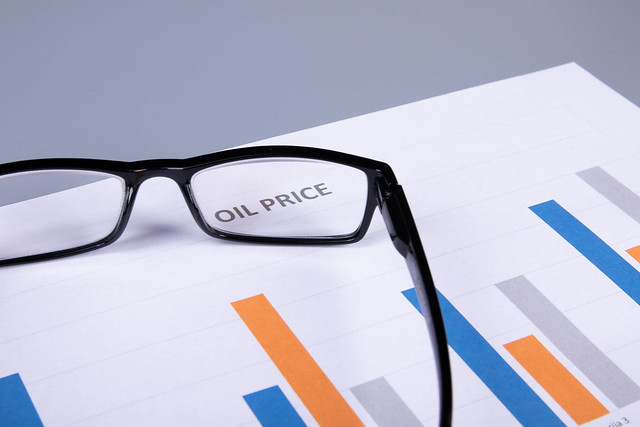 Glasses on a document with oil price chart