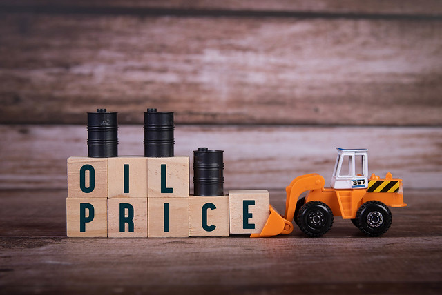 Wooden blocks with Oil Price text, oil barrels and bulldozer
