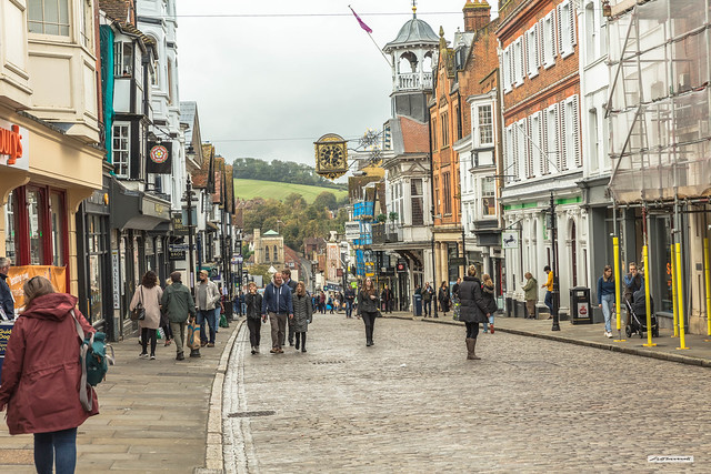 Guildford High Street with Guildhall Clock-Tower and St.Nicolas Parish Church, adjacent to the River Wey and its main bridge. Sunnydown, a part of the North Downs and an easterly extension of the Hog's Back is on the horizon, Surrey, England.
