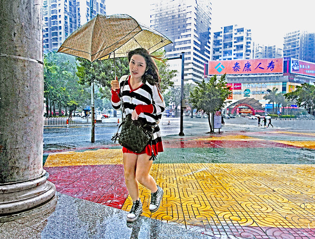 China 2011. Haikou. She rushes to shelter of monsoon rain.
