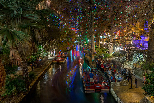 sanantonio downtown texas attraction sanantonioriver riverwalk holidaydecorations romjul nightexposure longexposure riverboats le tripod bridge canal water walkways urbanlandscape urban citylife canoneos70d palmtrees flare lifht holidaylights winter outdoor motion efs18135mmf3556isstm