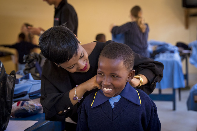 A staff member helps a new St Jude student with their uniform.