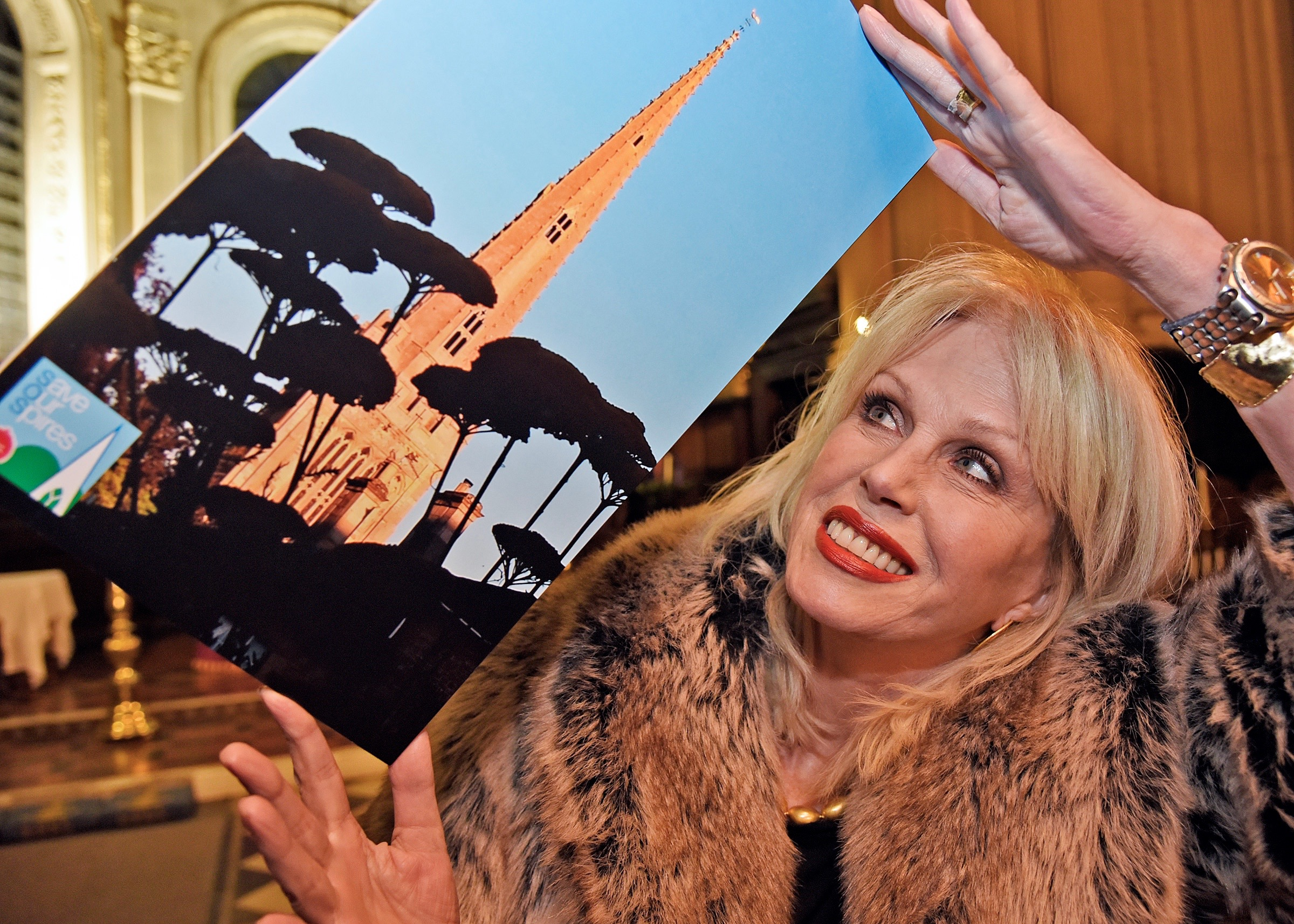 Joanna Lumley holding a photograph of St Peter's church in Oundle, Northamptonshire, taken by William Gunson