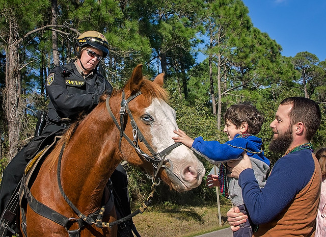 Mobile County Sheriff's deputy allows child to pet horse in the People's Parade during Mardi Gras in Dauphin Island, Alabama