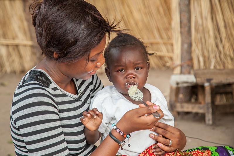 Angela Muyangana feeding the child of Namakando Mubiana, local farmer, Barotse Floodplain, Zambia. Photo by Clayton Smith.