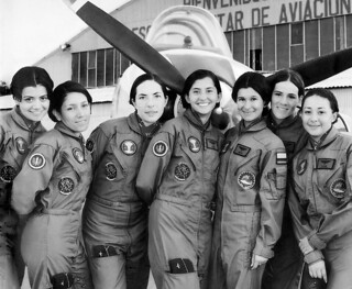 The first seven female pilot officers of the Colombian Air Force against a T-34