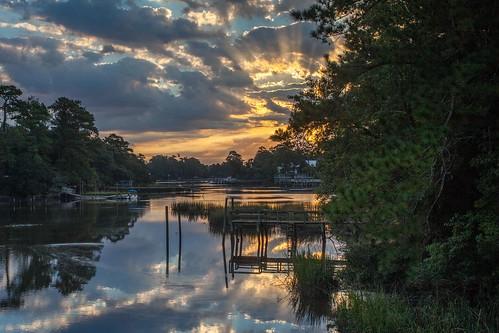 green water clouds creek sunrise boats pier dock rays