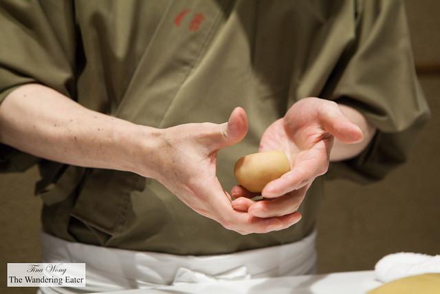 Chef rolling my chrysanthemum shaped namagashi (made of burnt orange colored white bean paste)