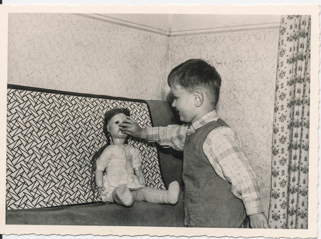 Little boy feeding a doll