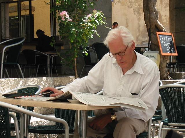 Gentleman's coffee cup gets lost under his newspaper
