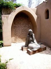 A bronze girl dreams by an old door