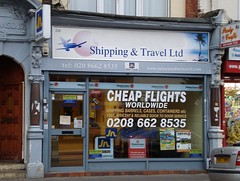 "A ground-floor shop with surrounds painted in a light blueish grey.  A sign above reads ""Shipping & Travel Ltd"", with pictures of an aeroplane and a palm tree to either side.  The fully-glazed shopfront is covered with decals advertising various services as well as a large proclamation of ""Cheap Flights Worldwide""."