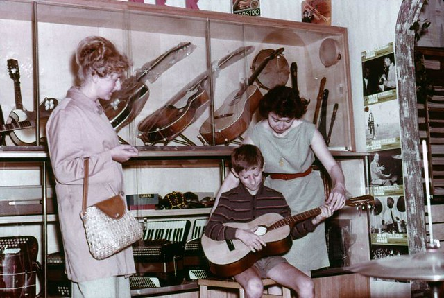 Gitarist in spe in muziekhandel / Testing guitar in a music shop