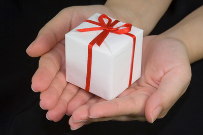 Hands holding out a small gift box