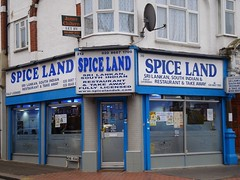 "The same ground-floor restaurant as in the first photo of this article.  It looks quite similar except that the windows are half-frosted, the sign is in blue and white instead of the grey it had in 2014, the name definitely reads ""Spice Land"" (two words) instead of ""Spiceland"" (one word), and it advertises South Indian food specifically instead of just Indian."