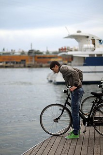 A man with a bicycle peering off the dock, Barcelona, Spain | by MsAdventuresinItaly