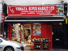"""A small terraced shopfront with a red surround and a sign above reading """"Vismaya Supermarket Ltd"""".  Bowls of fruit and bags of onions and potatoes are displayed outside on the pavement, and shelves holding packaged goods can be seen inside."""