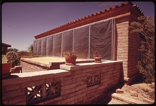 Side of a home near Tucson, Arizona has blackened panels under the plastic sheeting which heat circulating air..., 04/1974