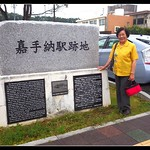 """A RIDER OF THE RAILS POSES BY THE KADENA RAILROAD STATION HISTORICAL MARKER """"MS. M"""" is now in her 80s, and has vivid memories of riding the OKINAWA RAILROAD during her Elementary School days.  Born in a village that was bulldozed by American troops working on the expansion of KADENA AIR BASE, her memories of pre-WW2 KADENA are still sharp.  She made clear to me that this Historical Railroad Marker erected in 2011 is not on the exact spot of the old Station, but only placed here because the real location is believed to be in the middle of old Highway 58, about 50 yards away --- .  I have posted close-up views of both blocks of text (one ENGLISH, the other JAPANESE), and the small illustration.    See the photostream or OKINAWA RAILROAD Set to find them.  Especially interesting to me was her vivid description of walking up the steep cobblestone path from Hija River Bridge to Kadena.   This """"path"""" --- flanked by steep cliff faces overgrown with large trees that made a long tunnel of shade --- was similar to the cobblestone path you can still see in Kinjo-Cho near Shuri Castle.  There is an old story (possibly fiction)  that tells of the Okinawans throwing boiling water mixed with sticky rice on the invading Japanese samurai who passed through here back in 1609.  This ancient and beautiful feature of Kadena was bulldozed, widened and graded by the US Military to make way for tank and truck traffic during WW2 --- today, it's the four-lane Highway 58 that goes down the hill from Kadena Circle to the Bridge.  *  MAIN CAPTION, RAILROAD STATS, LINE NAMES, and STATION COUNT is HERE :  www.flickr.com/photos/okinawa-soba/14029879002/  THE FULL FLICKr SET is HERE :  www.flickr.com/photos/okinawa-soba/sets/72157644364658344  沖縄鉄道   沖縄軽便鉄道   那覇軽便鉄道   沖縄電気鉄道   *  *  *  RANDOM SOBA :  www.flickriver.com/photos/24443965@N08/random/"""