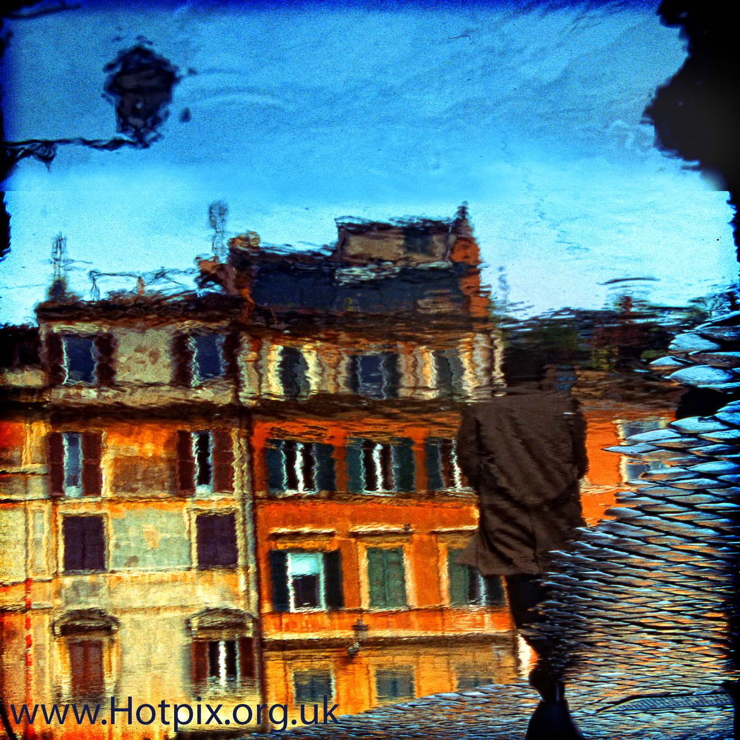 reflection,reflections,from,italy,italia,puddle,rain,wet,water,orange,buildings,building,square,piaza,man,person,male,walking,walker,Rome,Roma,Lazio,acutance,consulting,acutanceconsulting,acutanceconsulting.co.uk,www.acutanceconsulting