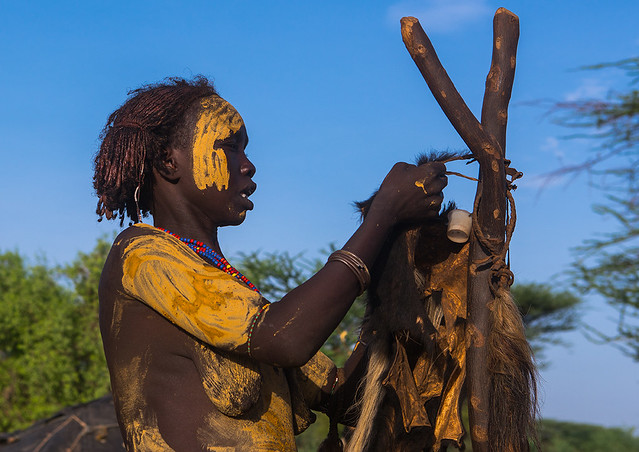 Dassanech tribe woman dressing for the dimi ceremony to celebrate the circumcision of the teenagers, Omo valley, Omorate, Ethiopia